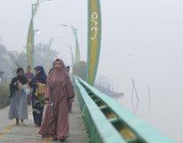 Umat Muslim yang akan menunaikan ibadah Salat Idul Adha berjalan di tepian Sungai Kapuas yang diselimuti kabut asap di Pontianak, Kalimantan Barat, 11 Agustus 2019. (ANTARA FOTO/Jessica Helena Wuysang)