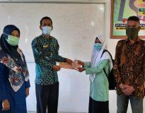 Kepala SMKN 1 lubuk Sikaping Muslim, M.Pd menyerahkan bantuan beasiswa, Jum'at (5/1/21).